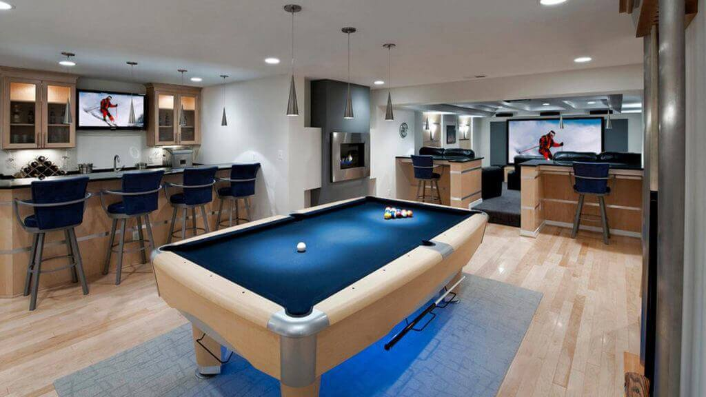 Photo of a finished basement with a pool table and a bar