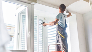 Image of person repairing drywall